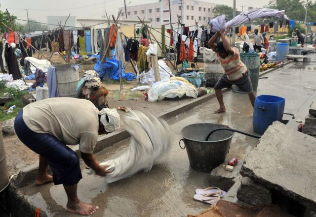 "Indian workers locally known as ""Dhobiwallahs"" wash clothes at Dhobhi Ghat in Hyderabad on March 26, 2010.  Dhobiwallahs are the human 'washing machines' of India, however the traditional community of workers washing clothes by hand is slowly disappearing with a combination of middle class families purchasing washing machines to use in their homes and a reluctance of the current descendants of dhobiwallahs to enter the procession.   TOPSHOTS   AFP PHOTO/ Noah SEELAM (Photo credit should read NOAH SEELAM/ AFP/ Getty Images)"